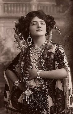 Bohemian excess!  Layers of lace and pattern, jewelry and stones, and best of all, an assiut shawl worn as a hipwrap.  Lovely.