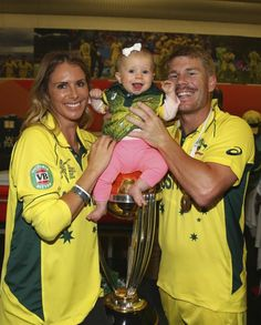 MELBOURNE, AUSTRALIA - MARCH 29: David Warner of Australia, his fiance Candice Falzon and their daughter Ivy Warner pose with the trophy in the changerooms during the 2015 ICC Cricket World Cup final match between Australia and New Zealand at Melbourne Cricket Ground on March 29, 2015 in Melbourne, Australia.