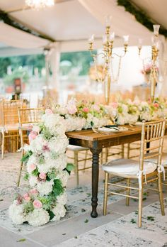 Fluffy white hydrangeas, greenery and pink flowers make an unbelievable centerpiece
