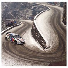 "VW Polo Rally Car fast approaching ""Hairpin Left, Don't Cut!!"" on a snow covered asphalt stage."