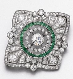 Diamond and Emerald Brooch, Circa 1920 The openwork plaque of quatrefoil shape set in the center with an old European-cut diamond weighing approximately .75 carat, completed by 118 smaller old European-cut and single-cut diamonds weighing approximately 3.25 carats, decorated further with a circle of calibré-cut emeralds, mounted in platinum.