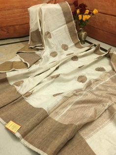 Feel of the richness of thoroughly woven Off White color Silk Mark Certified pure Jute Banarasi Saree. The propitious mandala motifs are smothered in Antique Gold Zari work all over the body. A flat broad border in lower skirt matches the entire look well and creates as eye-catchy.
