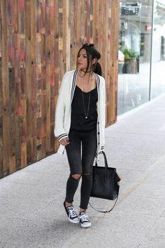 mujer con pantalon negro, sueter blanco y tenis converse