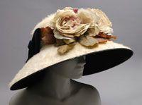 Woman's Hat. Made in Philadelphia, Pennsylvania, United States. 1910. Schmoele & Co., Philadelphia. Off-white furred felt, black silk velvet, artificial flowers. 7 x 17 1/2 inches (17.8 x 44.5 cm)