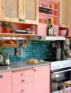 If you're going bright on kitchen cabinetry, create a contrast when it comes to your splashback tiles. Here, candyfloss pink is balanced out with stylish teal wall tiles. Click for more amazing kitchen tile ideas #homedecor Image: Earthly Urban Interiors