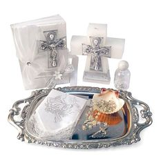 Babys Baptism Candle Gift Set Style SB3338- In Choice of Language Set includes cross shaped candle, new testament, clear rosary, shell, handkerchief, holy water bottle and silver tray. Each set comes in a gift box.  http://www.flowergirldressforless.com/mm5/merchant.mvc?Screen=PROD&Product_Code=AG_SB3338&Store_Code=Flower-Girl&Category_Code=New