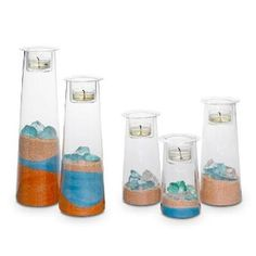 "Symmetry Set - Quintet of clear glass holders in graduated heights to customize your way. Fill the glass bases with your own decorative accents and finish by adding the votive cup on top. Light from a votive or tealight, sold separately, sets them aglow. Height: 5"" - 10¾"". Set of five. http://www.partylite.biz/legacy/sites/nikkihendrix/productcatalog?page=productdetail&sku=P91852S&categoryId=58466&showCrumbs=true"