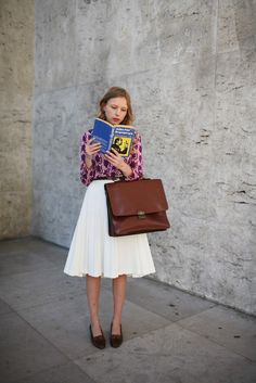 Men's briefcase and loafers paired with ultra feminine skirt outside the Paris shows.