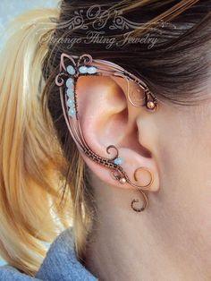 Un paio di polsini orecchio elfo è costituito da filo di rame e perline in vetro azzurro. Il pezzo è appannato, lucido e ricoperto di metallo