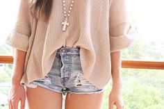 knit top. slashed shorts and long cross necklace.