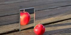 Little Apple is reflected in the mirror. But the reflection looks like the big Apple