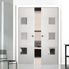 Double Pocket Ripple White sliding door system in three size widths with Clear Glass. #whitedoors #moderndoors #contemporarydoors