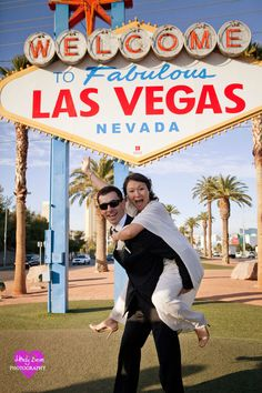 bride and groom fooling around by the Vegas sign