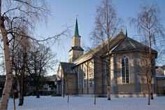 Late afternoon sunshine bathes old wooden Cathedral in Tromso, Norway on a cold winter afternoon