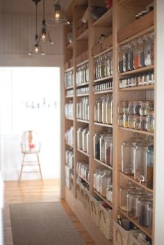 The key to open-shelved pantries lies in the collection of storage vessels; neatly arranged rows of glass jars add a uniform note to open shelving displays of bulk ingredients.