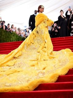 2015 Met Gala: Rihanna is wearing a long gold cape with embellishments and fur lining by Chinese designer Guo Pei. Spot on with the theme, Rihanna! One of the most talked about dress at the Met Gala! Only Rihanna can pull this exquisite cape off! Moda Rihanna, Estilo Rihanna, Looks Rihanna, Rihanna Style, Rihanna Dress, Beyonce Met Gala Dress, Rihanna Red Carpet Dresses, Beyonce Red Carpet, Rihanna Fashion