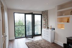 Bifold glass doors partially opened in a loft conversion NW london