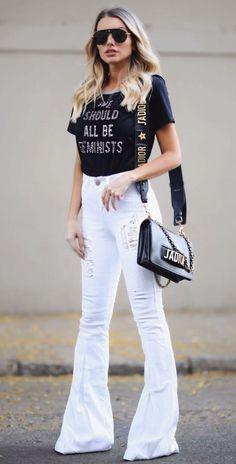 Musa do estilo: Bianca Petry. T-shirt preta estampada, calça jeans branca flare com detalhes destroyed