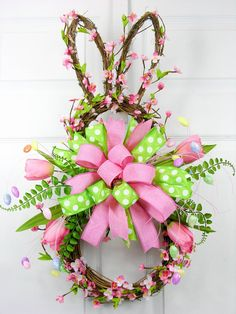 "A vine and pink cherry blossom grapevine bunny shaped wreath with a large pink/green dotted Terri Bow. The wreath has accents of whispy egg picks, tulips and fern. Measures 27""H X 18""W."