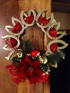 Christmas wreath made out of horse shoes and decorated with red and green accents. Use regular horse shoes and burlap, also.