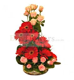Basket arrangement of Red Gerbera & Pink Roses with seasonal foliage. #FlowersDeliveryIndia #EasyFlowers