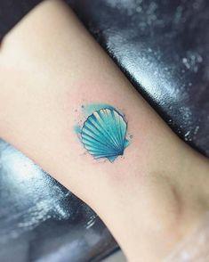 Tatuaje de una concha de color azul en estilo acuarela, situado en el tobillo.