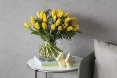 Påskeharene i keramikk er koselige sammen med gule påsketulipaner.