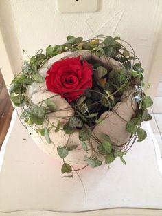 Betonkugel mit roter Rose