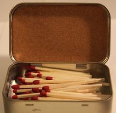 Altoid tin for matches, with sand paper glued to the inside of the lid.
