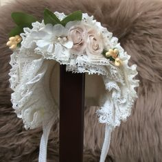 White silk bonnet, trimmend with lace and flowers.