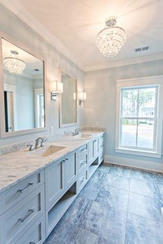wall length gray shaker vanity, painted Sherwin Williams On the Rocks, accented with nickel cabinet pulls, a white and gray marble counter, gray-blue walls, gray marble floors.