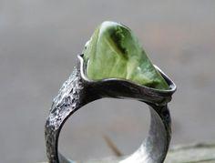 Autorský cínový prsten z bezolovnatého cínu, mědi a krásného prehnitu s epidotem  Kámen má světle zelenou barvu s tmavě zelenými vrostlicemi epidotu uvnitř, vnitřní kresba je velmi pěkná, velikost kamene je 1,4 x 1,7 x 1,2cm. Je usazen v cínu, zdoben cínovaným drátem a kuličkou cínu. Prstenec je ručně vyroben z cínované mědi, velikost je nastavitelná od 16 do 19mm - je třeba použít trochu násilí, prstenec je velmi pevný. Díky velké vrstvě cínu na prstenci se prsten nebude odírat, vhodný pro…