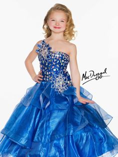 The Sugar pageant gown 81690S is a stunning one shoulder junior pageant dress with a fitted drop waist bodice that has been covered in sporadic chunky broken mirror rhinestones on a sequin fabric underlay. The skirt is made up of unique shimmering tulle that will add bling to this sparkling winning dress!