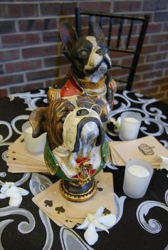 A pair of vintage poker bulldog busts accompanied by antique playing cards and dendrobium orchid scatter.