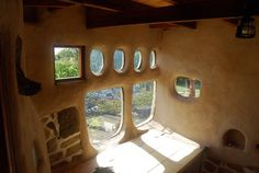 Building a cob or straw bale home allows you to be uber creative. Windows are like built-in art.