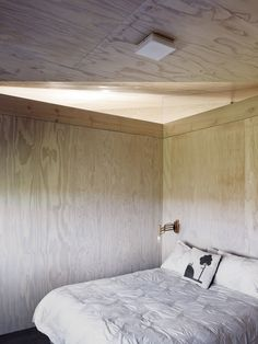 A guest bedroom is kept spare with a ceiling-mount light and vintage wood sconce. Villa Design, Cabin Design, House Design, Cabinet D Architecture, Interior Architecture, Interior Design, Wood Sconce, Plywood Interior, Kabine