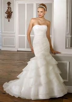 Wedding Dress 1606 1606 Simple yet chic, this Organza strapless wedding gown features asymmetrical pleating and a tiered ruffle skirt creating the perfect mermaid silhouette. Delicate beading accents