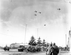 Troops of the 101st Airborne Division watch C-47's drop supplies to them in Bastogne, Belgium on December 26, 1944.