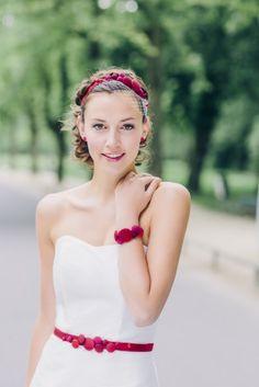 Kurzes, modernes Brautkleid mit Corsage und Herzausschnitt, rotem Band mit Knöpfen, passendem Armband und Fascinator.