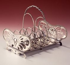 This is not contemporary - image from a gallery of vintage and/or antique objects. C. R. ASHBEE (1863-1942) An Arts & Crafts silver toast rack.