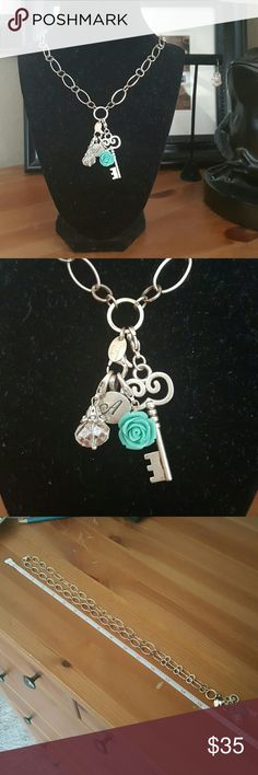 "Origami Owl Silver Charm Necklace Really pretty Origami Owl silver necklace with 4 charms. Key turquoise rose/flower, crystal and the letter ""A"" Used maybe 2 times. Origami Owl Jewelry Necklaces"