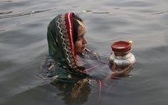 """Hindu devotee stands in waters of Sun Lake to offer prayers to Sun god during the Hindu religious festival """"Chhat Puja"""" in Chandigarh Hindu India, Prayer Photos, Right To Choose, India Style, Hindu Festivals, Chandigarh, India Fashion, Worship, Prayers"""