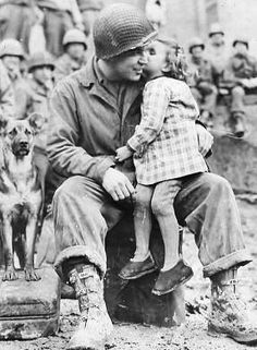 Elvin Harley of Kalamazoo Michigan of the 3rd Armored Division gets a peck on the cheek from a little French girl while listening to the 9th Armored Division Band near Aboncourt France. Photo dated February 14 1945 taken by Tec-5 L. G. Crabtree U.S. Signal Corps.