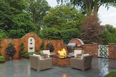 Residential Landscape Design Between One-half and One Acre | 1st - BACKER LANDSCAPING The addition of a moderate-size, in-ground pool is a central element. A built-in gas grill and a custom-built masonry gas fire pit also share the space. The original fountain was left intact, as were many of the brick walls. With the exception of pear trees and some shrubs adjacent to the new pool house, all of the landscaping, plant material, and landscape lighting was newly designed.