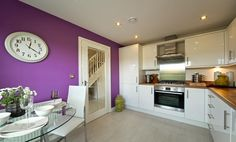 Taylor Wimpey have gone into the colour zone with an ultra modern interior designed small kitchen dining room with a bright violet accent wall - nice balance with the solid wood work tops - if they'd been black it would have killed it.