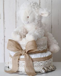 Two tier diaper cake made with 50 diapers size 1, wrapped with burlap and roped with a soft plush lamb. Diaper cake is made and ready to ship! You have any questions please feel free to message me