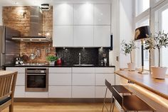 White kitchen, brick wall and mosaic