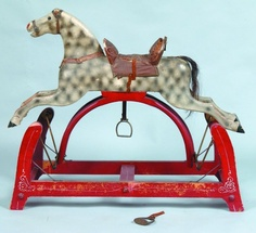 """Sold For $ 500     PA Carved and Painted Platform Rocking Horse, carved wooden horse with applied faux leather saddle and reins, metal stirrups and horse hair tail, metal swing hinges on wood base, horse painted white with smoke decorated highlights, red painted base with white line and stenciled highlights, 29-½""""h. x 35""""l. x 12-¾""""w., (minor losses to original paint)."""