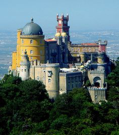 São Pedro de Penaferrim (The Pena National Palace), Sintra, Portugal... www.castlesandmanorhouses.com .... The Pena National Palace is a Romanticist palace on the top of a hill above the town of Sintra. On a clear day it can be easily seen from Lisbon. It is a national monument and notable expression of 19th-century Romanticism. The palace is a UNESCO World Heritage Site and one of the Seven Wonders of Portugal.