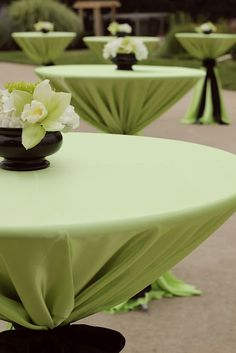 Full length tablecloths tied on high top cocktail tables keep linens from blowing during an oudoor catered reception.
